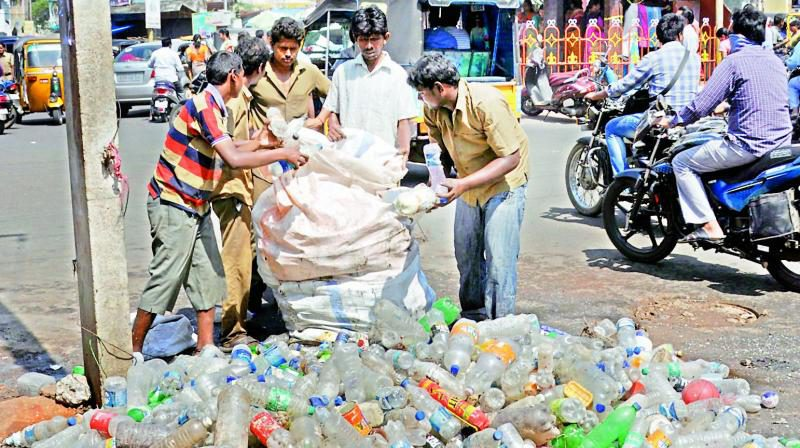 Civic staff remove plastic waste including bottles from an underground drainage line at Devi Chowk in Rajahmundry